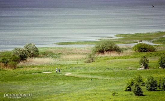 Площадка на берегу Плещеева озера, на которой лежит Синий камень. Собственно, он лежит чуть левее двух фигур, уже поклонившихся камню и направляющихся к кусту, на который паломники привязывают леточки. Этот куст в правой части снимка, беловатый от приношений у основания. Снимок сделан с Ярилиной горы