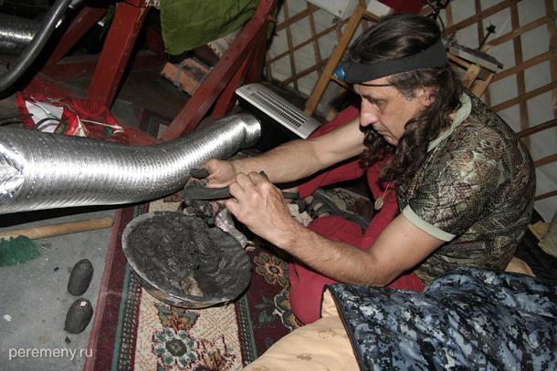 Александр Мамонтов заклеивает серебряные камни в глиняные матрешки - для следующей плавки. Уже подготовленные матрешки стоят перед ним.