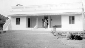 Рамана Махарши стоит на пороге коровника, построенного Аннамалаем