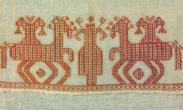 Эта вологодская вышивка изображает Мокошь. Кони (всадники) слева и справа от нее - два мужских божества, соперничающие за богиню. Эти боги сегодня известны под именами Николы и Георгия (а также Ильи). Подробнее о них будет сказано в текстах, посвященных дням силы этих богов