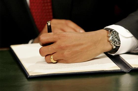 Барак Обама подписывает свой первый документ на посту президента США. Смотрите, он еще и левша. Вот не могу разобрать, сколько времени у него на часах