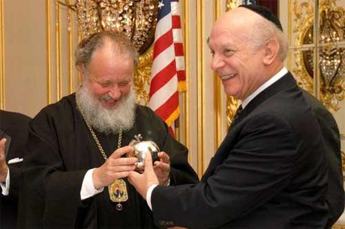 Митрополит Кирилл, как дитя, радуется золотому яблоку, которым его искушает Нью-Йоркский раввин Шнайдер