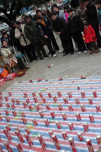 Китайцы играют в кока-колу. Набрасывают пластмассовые кольца на  банки. Прямоугольное поле из банок колы - 20 на 10 банок. Народная забава. Фото Глеба Давыдова