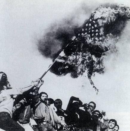 Иранцы жгут американский флаг на стене посольства США в Тегеране после его захвата 4 ноября 1979 года